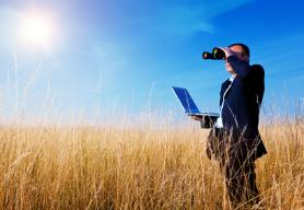 picking a domain name in a field on laptop with binoculars
